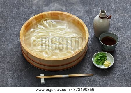 kamaage udon is a kind of japanese udon noodes dish, plain hot udon noodles in wooden pail and dipping sauce