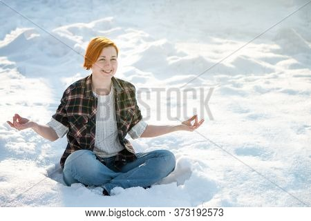 Beautiful Young Woman Meditates In Winter Park. Cute Ginger Girl In Lotus Pose Outdoor. Tranquility