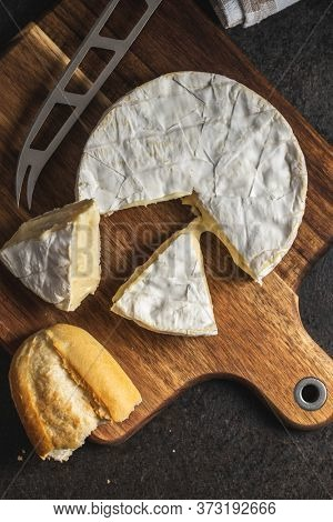 Brie cheese. White soft cheese with white mold on cutting board. Top view.