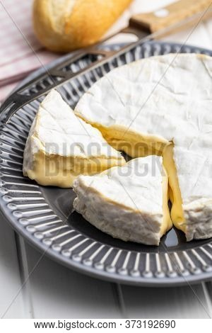 Brie cheese. White soft cheese with white mold on plate.