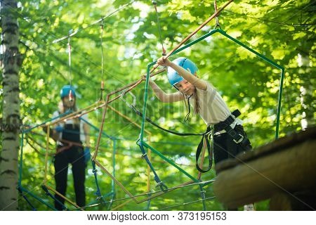 Rope Adventure - A Little Girl Walks On The Rope Bridge And Holding By The Ropes With Her Hands - He