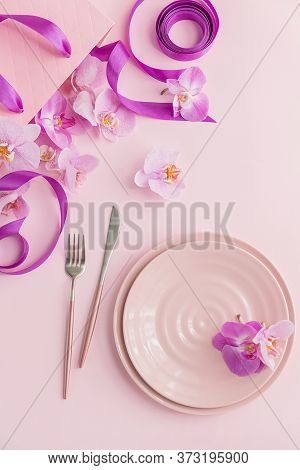 Flower And Table Settings Overhead Composition On Light Pink Background. Pink Ceramic Plates, Cutler