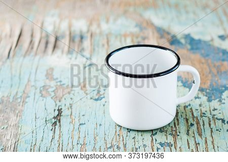 Empty White Enameled Mug On An Old Wooden Table. Dishes For Camping And Travel. Copy Space