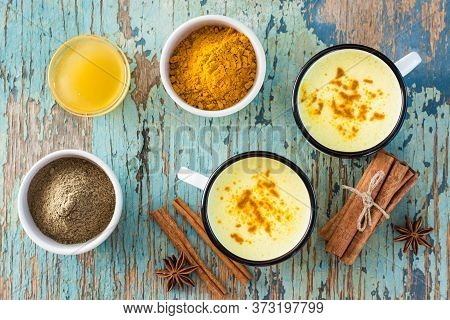 Detox Drink. Golden Milk With Turmeric And Cinnamon In Mugs And Ingredients For Cooking On A Wooden