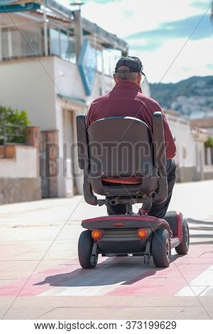 Elderly Disabled Person Or Senior On Electric Wheelchair Or A Mobility Scooter Driving On The Promen