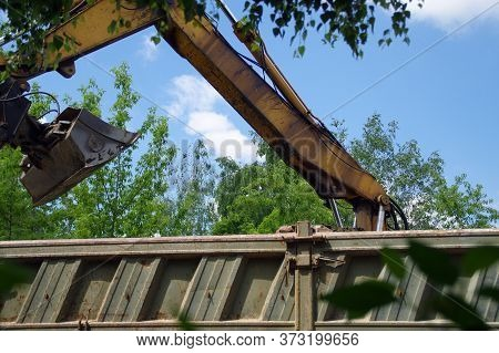 Excavator Load Soil On Truck. Digger Machine On Construction Site. Heavy Industry Business.
