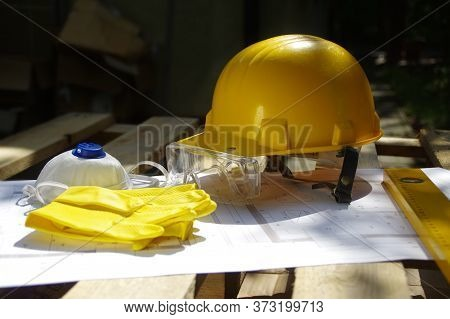 Helmet, Goggles, Mask And Gloves. Personal Protective Equipment On Construction Site. Heavy Industry