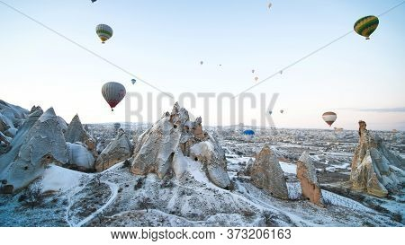 Cappadocia, Turkey - January 6, 2020: Colorful Balloons Over Volcanic Rocks In Cappadocia. Turkey.