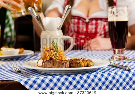 Young people in traditional Bavarian Tracht eating in restaurant or pub lunch or dinner