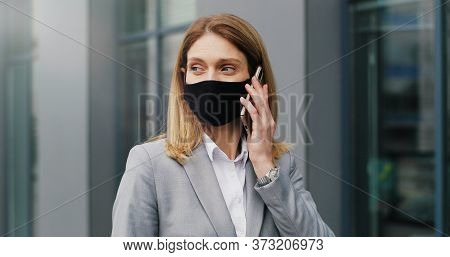 Caucasian Young Woman In Mask Walking The Street And Talking On Mobile Phone. Female Pedestrian In R