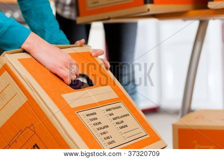 Young woman - presumably friends - with moving box in her house moving in or out of a apartment, focus on moving box