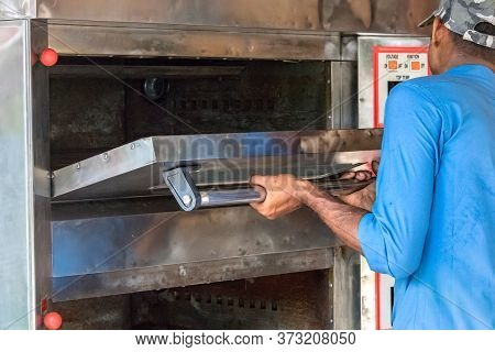 Praslin, Seychelles - February 5th, 2019: One Repairman Fixing The Door Of An Electric Oven In Prasl