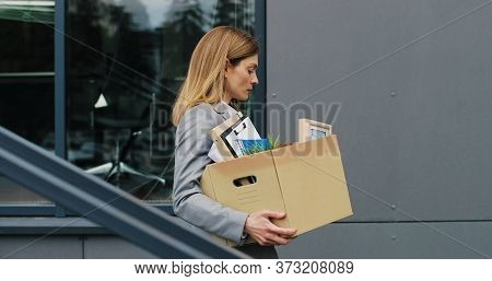 Caucasian Upset Businesswoman Walking Down The Stairs Outdoors With Box Of Stuff As Leaving Business