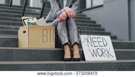 Portrait Of Caucasian Young Unemployed Woman Sitting Outdoors At Stairs With Poster Need Work. Femal