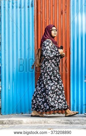 Male, Maldives - February 11th, 2019: A Woman Wearing Hijab And Abaya Walking Over A Corrugated Wall