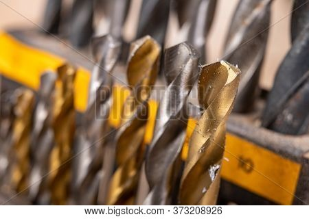 Metal drill bits placed in a stand. Accessories in a home workshop. Workplace garage at home.