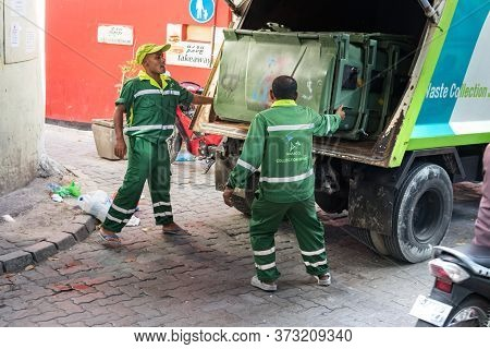 Male, Maldives - February 11th, 2019: Two Garbage Collectors Loading A Trash Bin On A Truck In Male,