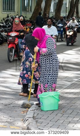 Male, Maldives - February 11th, 2019: A Muslim Woman Wearing Hijab Sweeping And Cleaning The Street