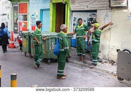 Male, Maldives - February 11th, 2019: Four Garbage Collectors Talking Making A Break In Male, Maldiv