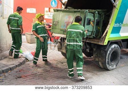 Male, Maldives - February 11th, 2019: Three Garbage Collectors Loading A Trash Bin On A Truck In Mal