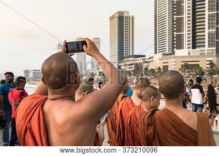 Colombo, Sri Lanka - February 19, 2019: A Group Of Buddhist Monks With Orange Clothes Looking The Ci