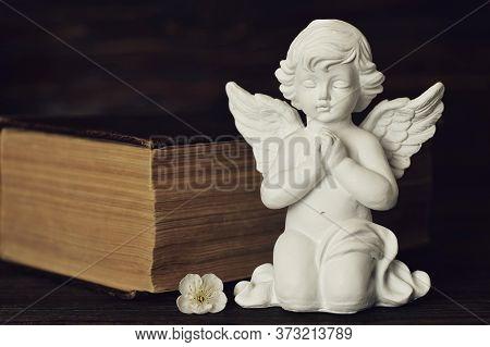 Guardian Angel Kneeling And Praying On Dark Background