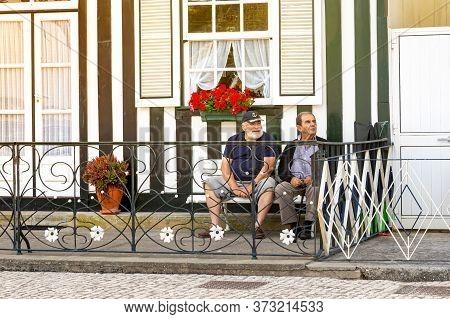 Two Senior Men Relax Next To A Typical Striped Fishing Houses Costa Nova, Aveiro, Portugal. Costa No