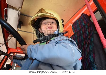 Little Boy Acting Like A Fireman. Boy Sitting In A Real Fireman Car. Happy Adorable Child Boy With F
