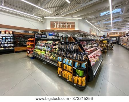 Interior View Of A Supermarket With Aisle With Shelves Full Of Fruit And Vegetable Variety Of Produc
