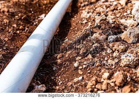 Pvc Pipe In Dirt Trench Outdoors For Plumbing Water Drainage Installation. Underground Irrigation Sy