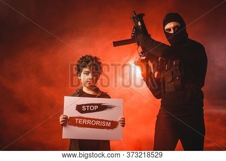 In Balaclava Holding Machine Gun Near Muslim Boy With Stop Terrorism Lettering On Card On Black Back