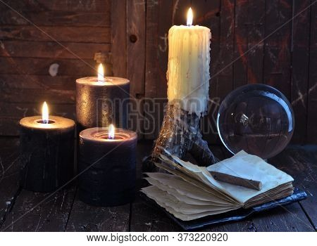 Creepy Still Life With Burning Candles, Crystal Ball And Open Diary On Witch Table. Esoteric, Wicca