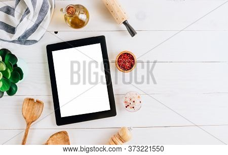 Tablet With Blank Screen And Different Kitchen And Cooking Utensils On Whie Wooden Table. Culinary B