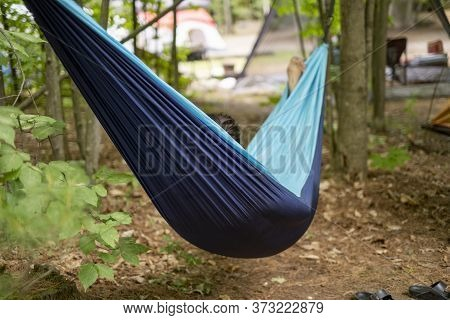 Woman Relaxing In A Hammock While Camping In Summer