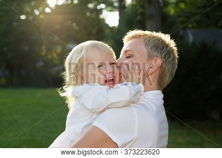 Mother carrying daughter (3-4) in garden girl crying