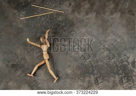 Puppet In The Hands Of Puppeteer Walks On Isolated, Background. The Concept Of Manipulation. Copy Sp