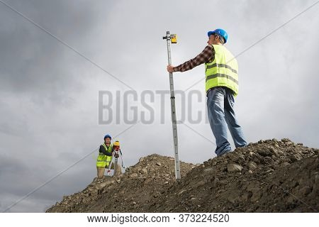 Surveyors using theodolite on building site