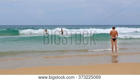Back View Of Women At The Beautiful Scenery Of Beach.
