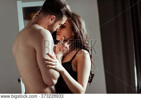 Sexy Young Couple Kissing At Home Near Brown Curtains