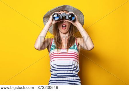 Young Woman In Shock In Surprise With A Hat And A Striped Dress Looks In Surprise With Binoculars On