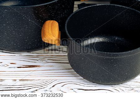 New Black Cookware With Wooden Handles Close Up