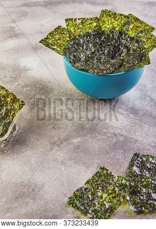 Crispy Nori Seaweed In A Blue Bowl On A Gray Background. Japanese Food Nori. Dried Sheets Of Seaweed