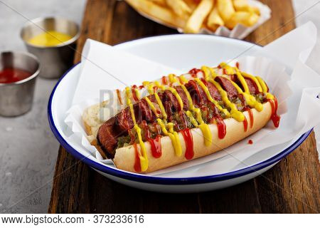 Grilled Bacon Wrapped Hot Dog With Relish, Ketchup And Mustard
