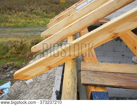 A Close-up On Unfinished Roofing Construction, Roof Framing, Wooden Beams, Rafters, Trusses, Purling