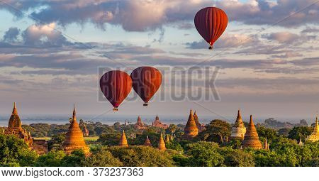 3 Red Hot Air Balloons Above Colorful Ancient Temples At Sunrise In Bagan, Myanmar