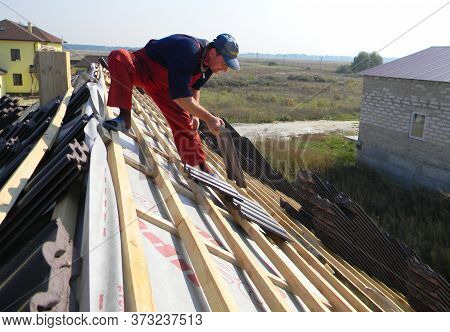 Kyiv, Ukraine - June, 28, 2020 A Building Contractor On The Ridge Of The Roof Of A House Constructio