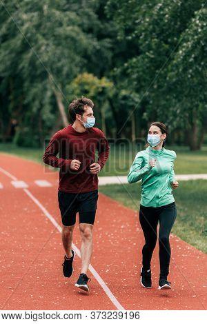 In Medical Masks Jogging Together On Running Path In Park