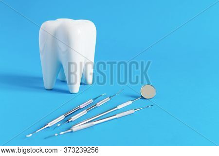 White Dental Tooth Model With Dentistry Tools For Teeth Dental Care On Blue Background.