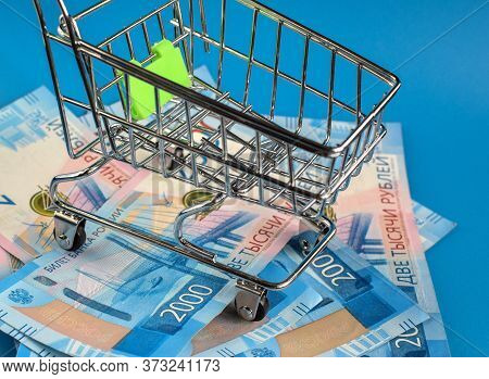 Russian Rubles Under The Basket On A Blue Background. Empty Grocery Cart On The Background Of 2000 R