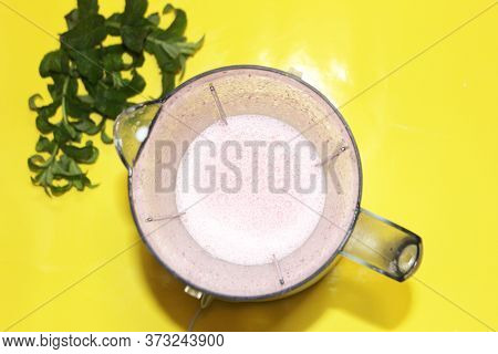 Milk  Smoothie Is Mixed In A Mixer On A Yellow Background With Mint. Milk Are Mixed In A Blender On